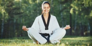 Martial Arts Lessons for Adults in Angleton TX - Happy Woman Meditated Sitting Background